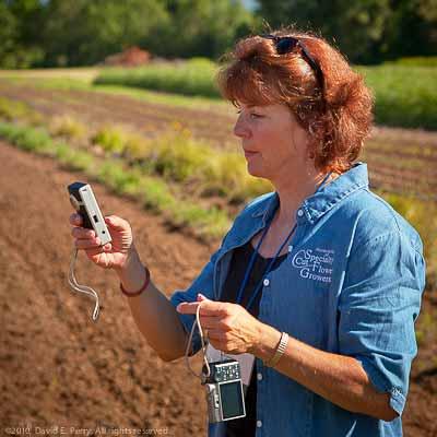 A woman in a field holding a digital camera