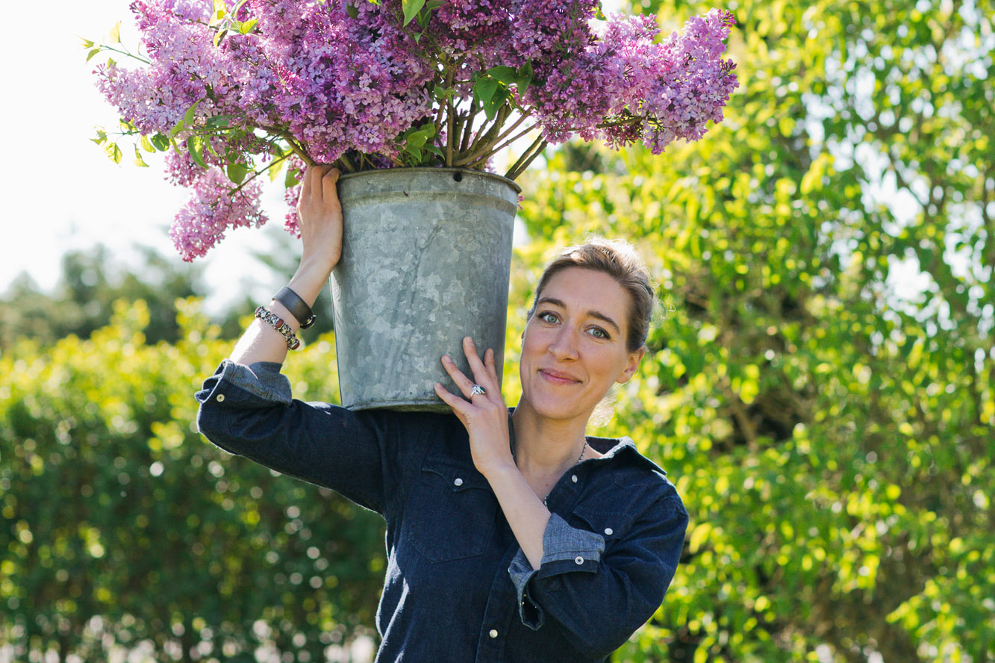Erin Benzakein balancing a bucket of lilacs on her shoulder
