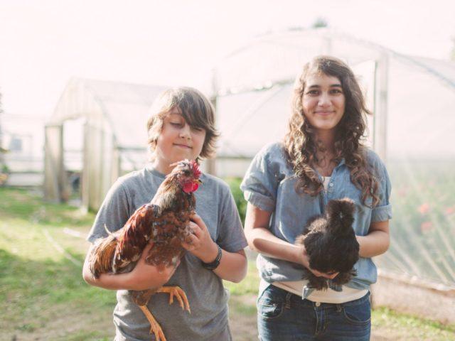 Elora and Jasper Benzakein holding chickens