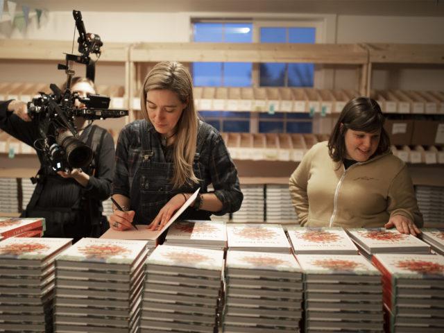 Erin Benzakein and Jill Jorgensen signing books while being filmed