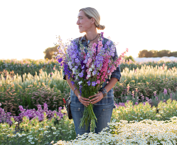 Erin Benzakein standing in the field holding a handful of larkspur