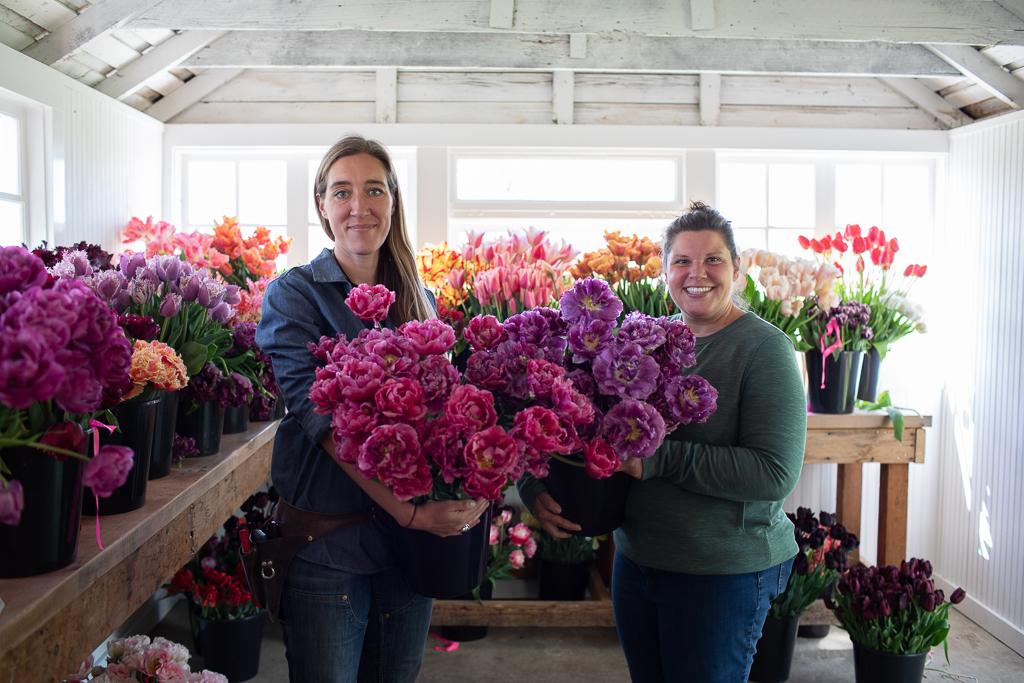Erin Benzakein and Jill Jorgensen holding buckets of specialty tulips in the Floret studio