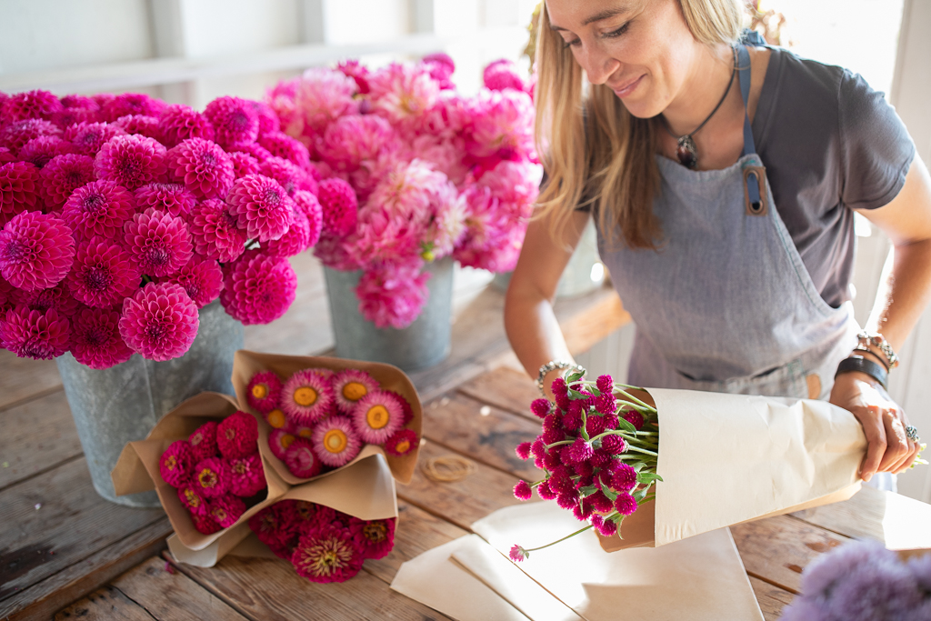 Erin Benzakein packaging bouquets of pink flowers into kraft paper sleeves in the Floret studio